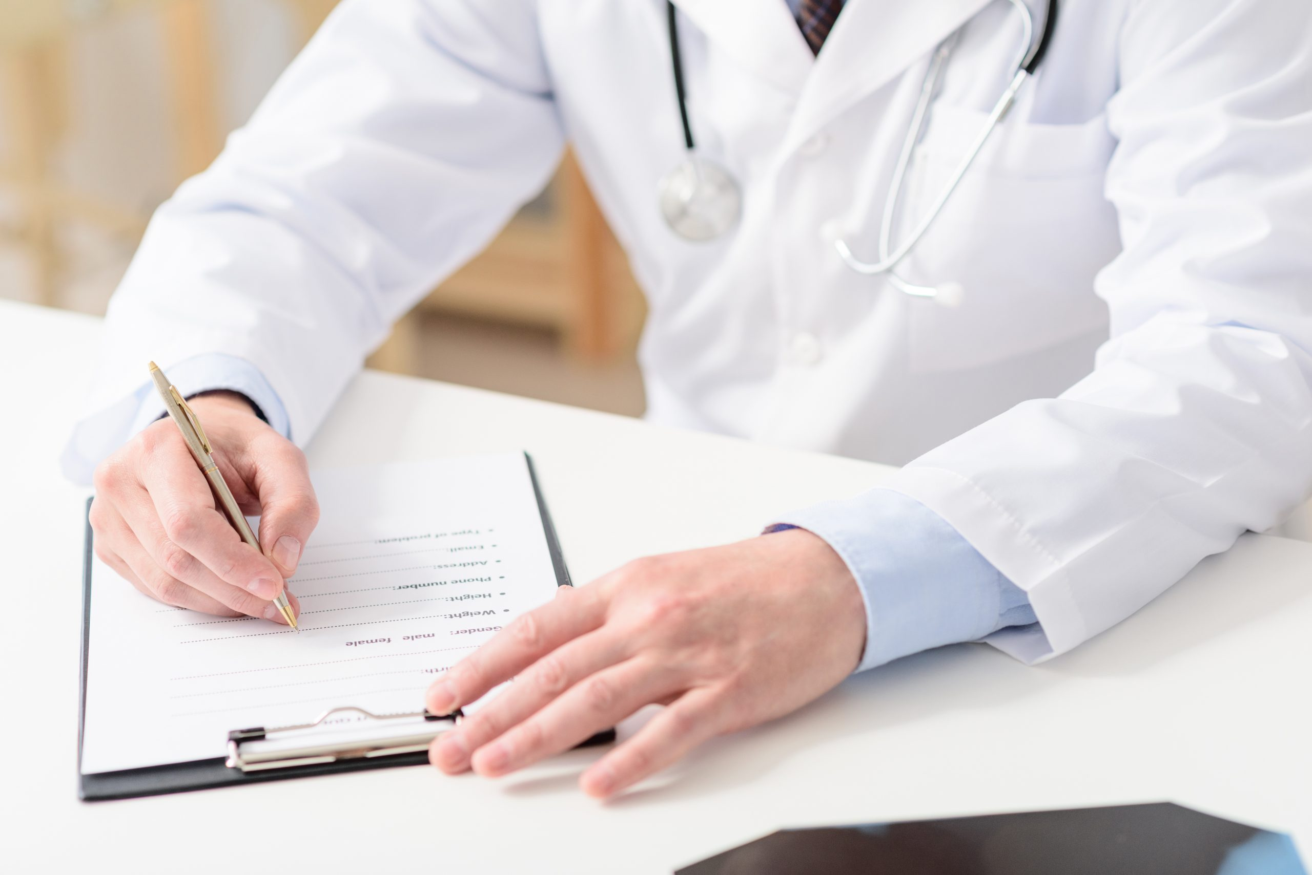 Accessing medical records. Close up of doctor writing on his clipboard, sitting in his office