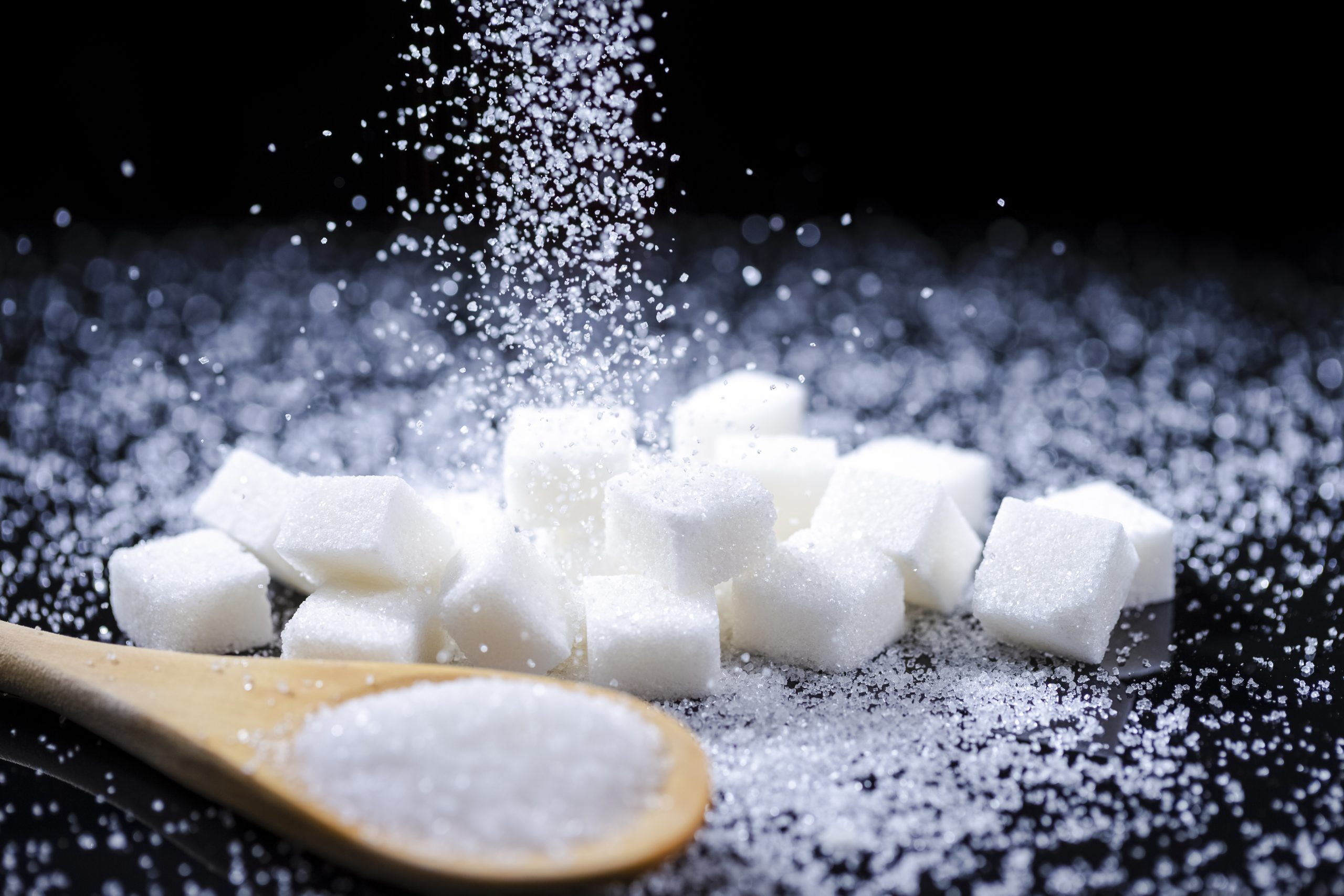 Macro Shot of White Cube Sugar And Falling Sand Sugar Along With Filled Wooden Measure Spoon. Against Black Background. Horizontal Orientation
